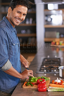 Buy stock photo Shot of a handsome young man chopping vegetables on the kitchen counter