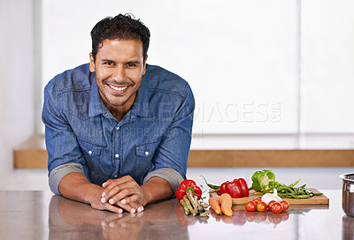 Buy stock photo A happy man leaning on his kitchen counter next to some vegetables