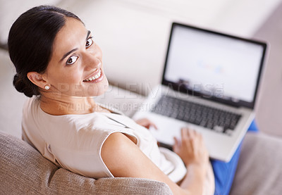 Buy stock photo Over the shoulder shot of a young woman sitting on a sofa using a laptop