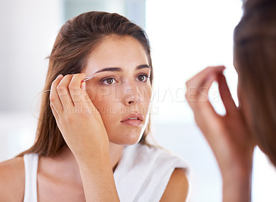 Buy stock photo A young woman tweezing her eyebrows in front of a mirror