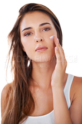 Buy stock photo Shot of a beautiful woman applying moisturizer to her face