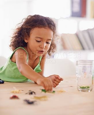 Buy stock photo Shot of a cute little girl playing with toy insects at home