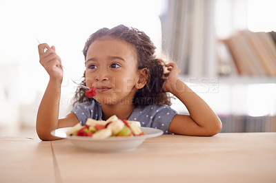 Buy stock photo Shot of a cute little girl eating fruit salad at a table