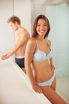 Buy stock photo Lingerie model at bathroom with a man washing his hands at the back