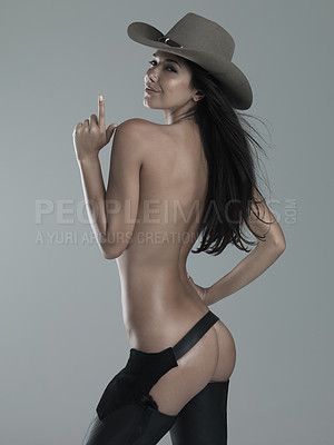 Buy stock photo Shot of a naked woman with a cowboy hat on a gray background