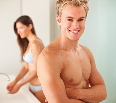 Buy stock photo Confident man at the bathroom with his wife at the back