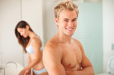 Buy stock photo Handsome man in the bathroom with wife at the back