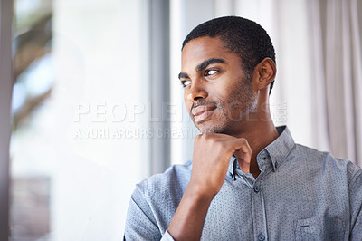 Buy stock photo Shot of a handsome young man thinking while looking through the window