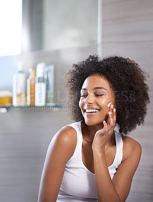 Buy stock photo An attractive young woman applying cream to her face