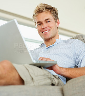 Buy stock photo A smart confident young man working on a laptop