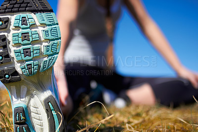 Buy stock photo Cropped shot of the sole of a woman's running shoe while stretching