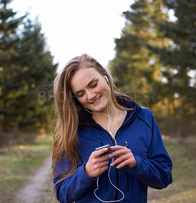 Buy stock photo Shot of an attractive and sporty young woman preparing her playlist before a run