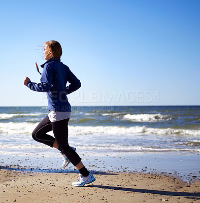 Buy stock photo A sporty young woman  running along the beach