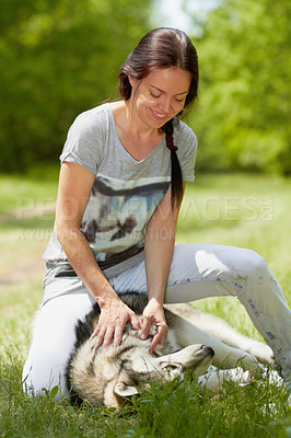 Buy stock photo Shot of a beautiful woman playing with her young husky dog in a park