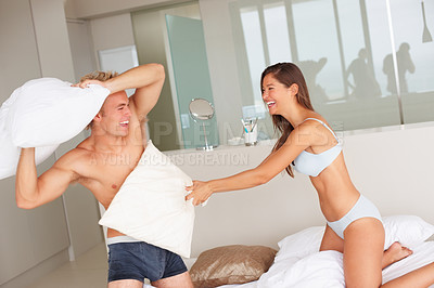 Buy stock photo Cute young couple enjoying a pillow fight at home