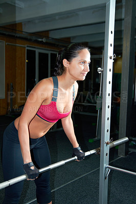 Buy stock photo Shot of an attractive young woman pumping iron in the gym