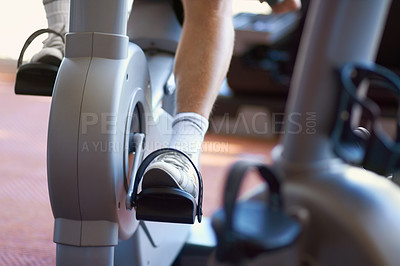 Buy stock photo Cropped shot of a man on an exercise bike at the gym