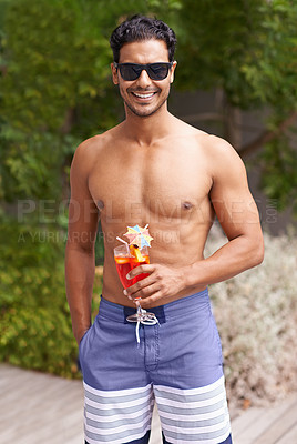Buy stock photo Portrait of a handsome man by a pool holding a cocktail