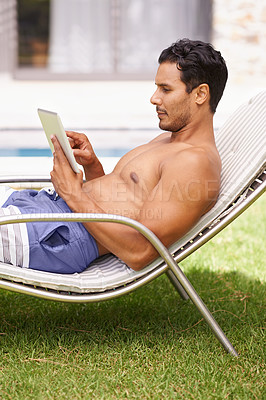 Buy stock photo Shot of a man reading a book while sitting in a deckchair