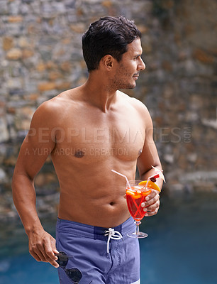 Buy stock photo Shot of a handsome man by a pool holding a cocktail