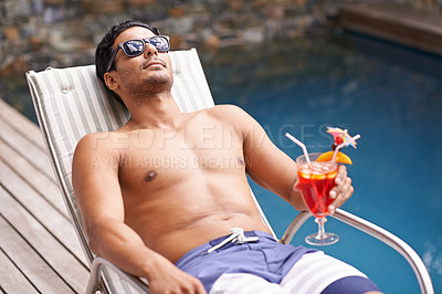 Buy stock photo Cropped shot of a man holding a cocktail while sitting in a deckchair beside a po