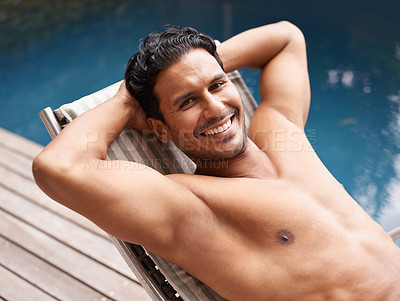 Buy stock photo Portrait of a young man sitting in a deckchair by a swimming pool