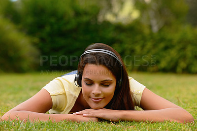 Buy stock photo Shot of a young woman lying on grass with her eyes closed