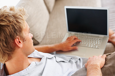 Buy stock photo Young man working on a portable laptop while sitting on the couch