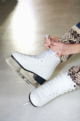 Buy stock photo Cropped shot of a woman sitting on ice tying up her ice skates