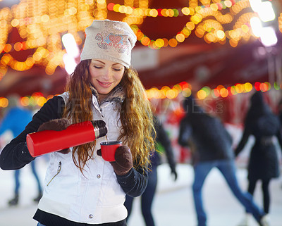 Buy stock photo A young woman standing outside on a winter's day pouring a warm drink from a flask