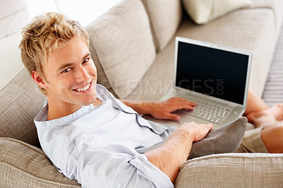 Buy stock photo Portrait of a handsome man at home working on a laptop