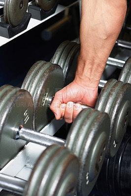 Buy stock photo Cropped image of a man picking up a dumbell