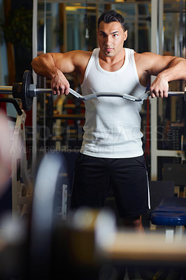 Buy stock photo A young man lifting a dumbbell at the gym