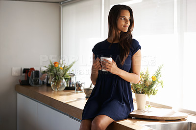 Buy stock photo Cropped shot of an attractive young woman standing in her kitchen while drinking coffee