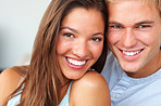 Charming young couple sitting together smiling