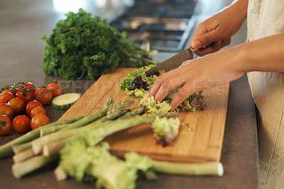 Buy stock photo Shot of a woman cutting up vegetables on a chopping boards