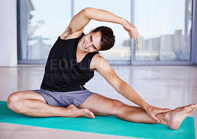 Buy stock photo A happy young man stretching on an exercise mat at home