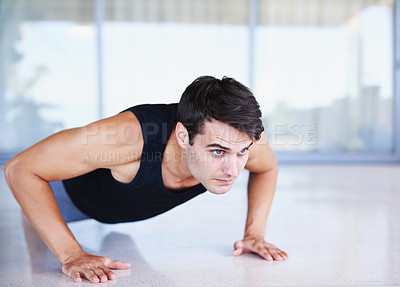 Buy stock photo A cropped shot of a focused young man doing strength exercises at home