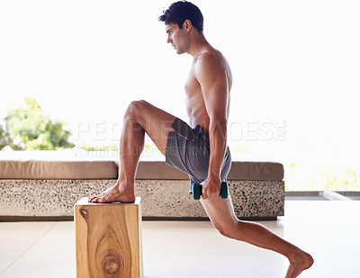Buy stock photo A muscular young man doing strength exercises with dumbbells at home