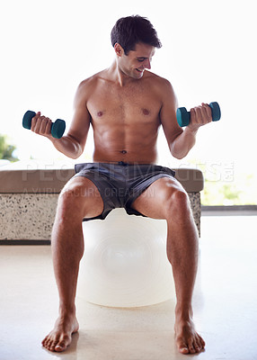 Buy stock photo A muscular young man lifting dumbbells while sitting on an exercise ball