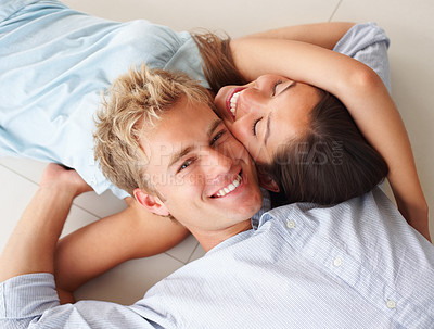 Buy stock photo Happy couple lying down on the floor and having fun