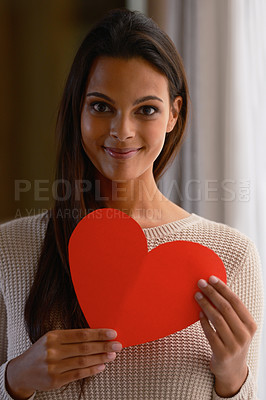 Buy stock photo Portrait of an attractive young woman holding a red heart shaped card