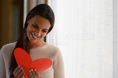 Buy stock photo Shot of an attractive young woman reading a valentine's day card at home
