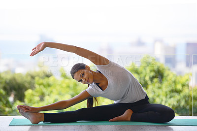 Buy stock photo Portrait of an attractive young woman stretching on a yoga mat