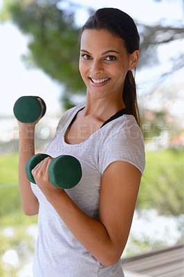 Buy stock photo Portrait of a beautiful woman lifting dumbbells by a window