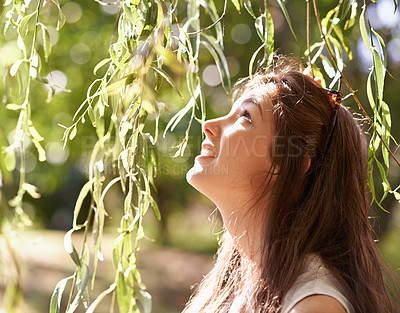 Buy stock photo Shot of an attractive teenage girl standing by a willow tree