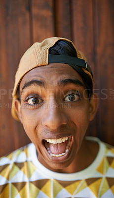 Buy stock photo Portrait of a teenage boy making a face while standing against a wooden wall