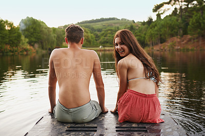 Buy stock photo Shot of two teenagers sitting on the end of a pier on a lake