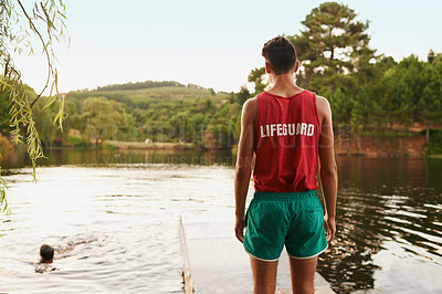 Buy stock photo Rear view shot of teenage boy wearing a lifeguard shirt looking out onto a lake while his friend swims
