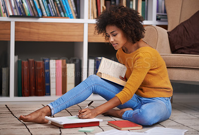 Buy stock photo Cropped shot of an attractive young woman sitting on the floor while studying